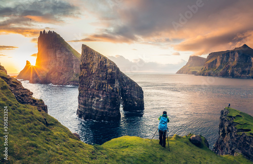 Obraz Photographer taking pictures to Drangarnir and Tindhólmur at sunset in the Faroe Islands - fototapety do salonu
