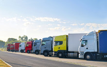 Various Types Of Trucks In The Parking Lot Next To The Motorway.