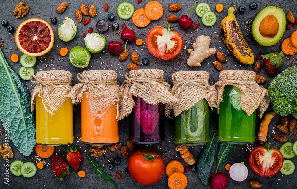 Fototapeta Colourful healthy smoothies and juices in bottles with fresh tropical fruit and superfoods on dark stone background with copy space.
