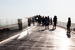 Silhouette people on the old wooden boat bridge.