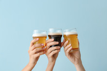 Hands With Glasses Of Beer On Color Background