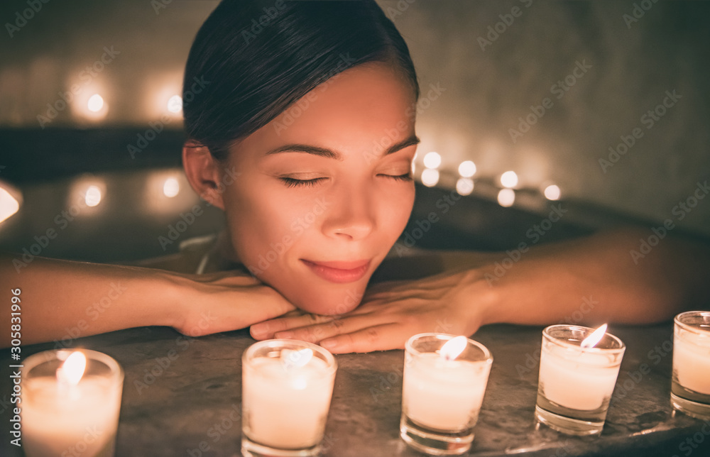 Fototapeta Spa relaxation Asian woman relaxing in hot tub jacuzzi luxury pamper resort. Sleeping girl next to candles, romantic night getaway.