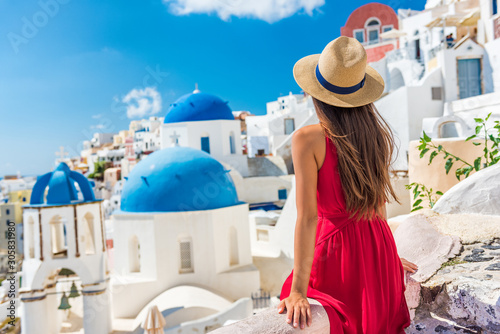 Fototapeta Europe holiday Santorini vacation girl in hat and red dress enjoying view of 3 blue domes famous tourist attraction in Europe. Summer sun holiday. obraz