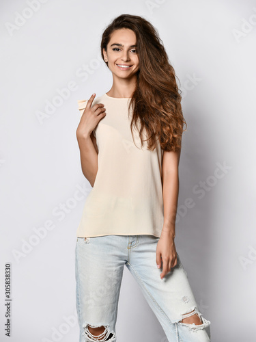 Fashion model wearing ripped boyfriend jeans, white blouse shirt. Fashion urban outfit. Casual everyday clothing style. Wall mural