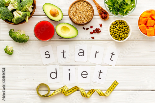 Fotografía Start diet text near healthy food on white wooden background top view