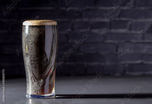 Stampa su Tela A dark Irish dry stout beer glass with a black brick on the background