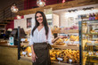 Smiling businesswoman welcoming guests near cashier and fridge