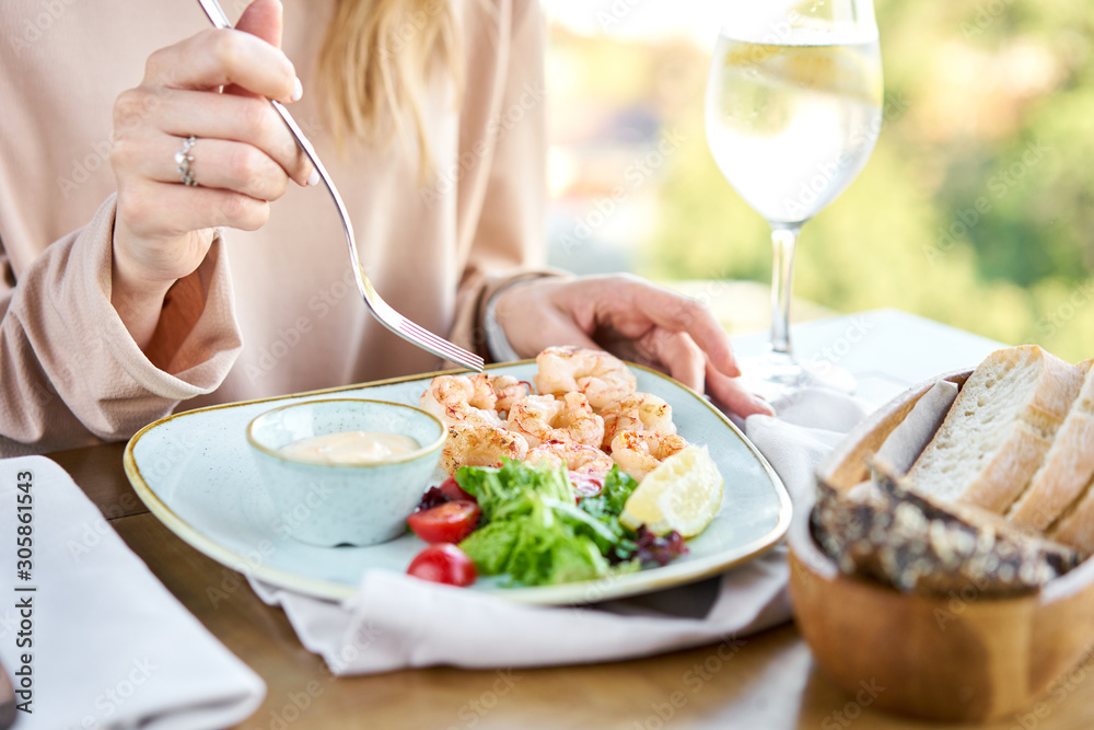 Fototapety, obrazy: Grilled Argentine shrimp with mango-jalapeno sauce. Lunch in a restaurant, a woman eats delicious and healthy food. Delicious fresh seafood prawns with fresh vegetables and lime. Cream sauce