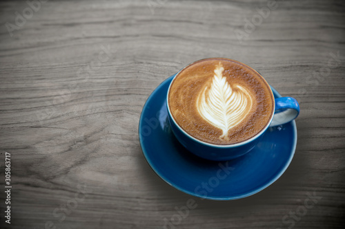A cup of hot latte coffee with latte milk art on the wood table , vintage tone color