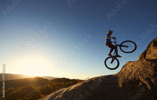 Leinwand Poster Professional sportsman cyclist jumping on trial bicycle on top of rocky mountain