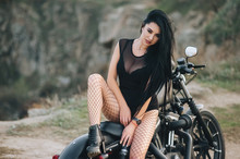 Beautiful Brunette Girl With Long Hair In A Black Dress And Stockings Sits And Poses On An Expensive Motorcycle On A Background Of Nature. Portrait Of A Sexy Woman On A Bike. Photography, Concept.