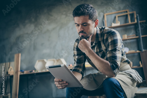 Fotomural  Photo of handsome serious guy holding e-reader website checking email online ord