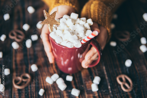 Foto auf Leinwand Schokolade Girl in yellow sweater holding hot chocolate mug covered with marshmallow