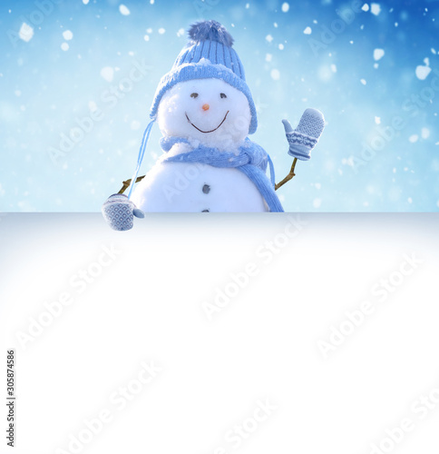 Poster de jardin Individuel Merry Christmas and happy New Year greeting card. Snowman standing in winter Christmas landscape and points to a white billboard.