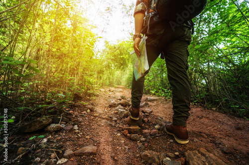 Fototapeta close up hiking man with trekking boots walking in the forest obraz