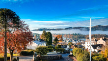Aerial Top View Over Bowness On Windermere On An Early Morning With Fog And Mist Rising On Lake Windermere. Autumn In The Lake District, Cumbria, UK.
