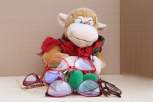 Toy Teddy Monkey In Glasses Will Tie With Pins And In Front Of It Multicolored Glasses To Choose From