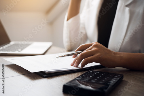 Fotografía  Women are sitting analyzing the company's financial statement plan using a calculator on his desk