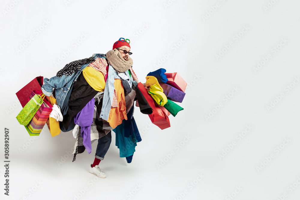 Fototapeta Shopping like an issue. Man addicted of sales. Overproduction and crazy demand. Female model wearing too much colorful clothes, need more. Fashion, style, black friday, sale, abusing purchases