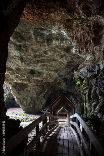 A wooden bridge at the entrance of Smoo Cave, a large combined sea cave and freshwater cave in Durness in Sutherland, Highland, Scotland, UK.
