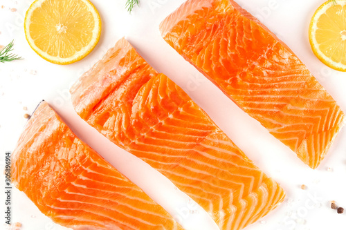 Fotografía  Slices of salmon with lemon, a flat lay close-up top-down shot with salt and pep
