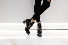 Closeup Of Female Legs In Black Jeans In Lacquered Black Boots On Silver Heels Near A White Wall In The Room. Fashionable Girl Is Standing In Stylish Footwear In A Store. New Seasonal Shoe Collection.