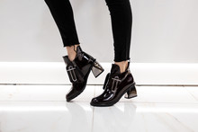 Closeup Of Female Legs In Vintage Jeans In Fashionable Patent Black Boots With Silver Heel. Girl Stands In A Shopping Center And Chooses Autumn Shoes. New Collection Of Women's Seasonal Footwear.