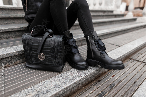 obraz dibond Young woman sits on stone steps outdoors in jeans in black fashion boots with a stylish leather handbag. Сlose-up of female legs in fashionable shoes with a trendy bag. Autumn winter collection.