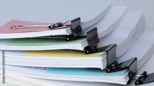 Obraz Old office working document with pastel note paper and black paper clip folder on white background - fototapety do salonu