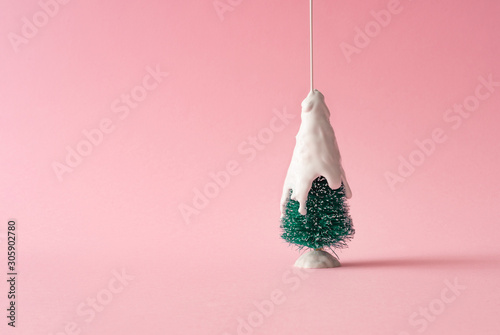 Christmas tree with white dripping paint as snow against pastel pink background. Minimal creative holiday concept.