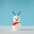 Leinwanddruck Bild - Snowman on bright blue background with reindeer nose and antlers. Winter holiday concept. Christmas minimal idea.