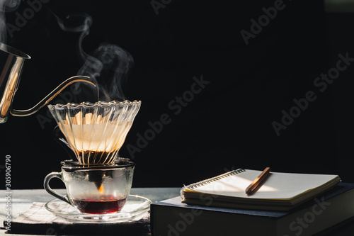 Tuinposter koffiebar The steam from a cup or a pot of coffee on the old wood table and black background with a book,notebook,pencil, Warm drinks make good healthy, Drip coffee brew, easy to make at home, Selective focus.