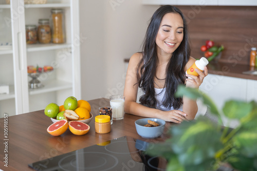 Fototapeta Young woman taking a nutritional supplement at breakfast obraz