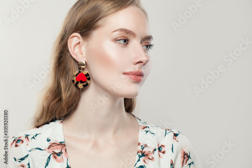 Photo Perfect beautiful woman wearing fashion golden earrings with red heart on white