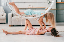 Two Excited Model Girls Have Fun In Interior Studio. Little Beautiful Girl In Pink Dress Lying Under Swing With Her Friend Lying On It.