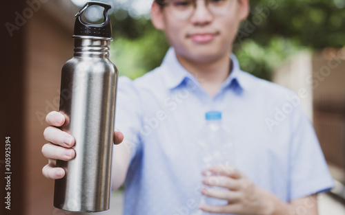Closeup portrait, Young asian man's showing a stainless steel reusable water bottle replacing a single use plastic drinking bottle which is a huge daily waste. World environment problem awareness.