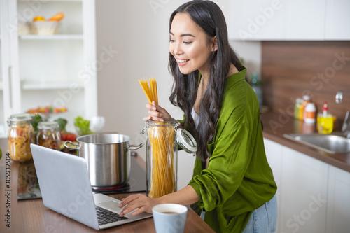 Pretty girl searching for a spaghetti recipe Fototapeta