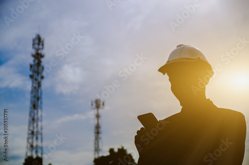 Leinwand Poster Silhouette of Engineer holding a mobile phone with telecommunication antenna and sunset background