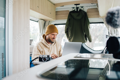 Work and Travel with Campervan in Australia young man is working in his van duri Wallpaper Mural