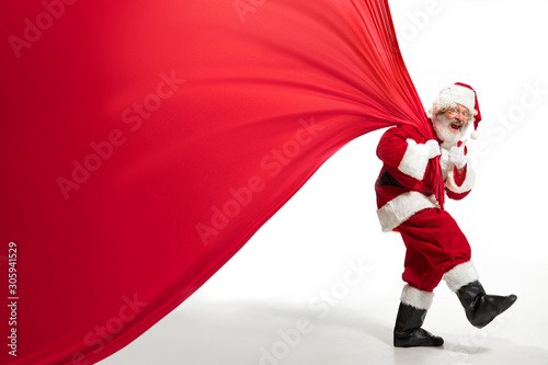 Poster Ecole de Danse Santa Claus pulling huge bag full of christmas presents isolated on white background. Caucasian male model in traditional costume. New Year 2020, gifts, holidays, winter mood. Copyspace for your ad.