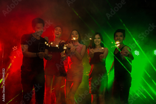 Holiday celebrations concept, Traveller people dancing together with enjoying at colourful night party club. - 305944332