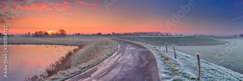 Foto Typical Dutch landscape with a dike, in winter at sunrise