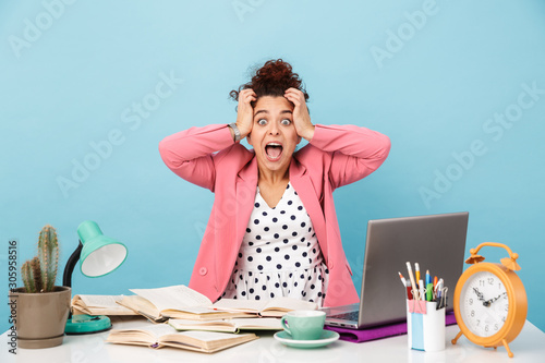 Photo Image of annoyed young woman screaming and grabbing her head