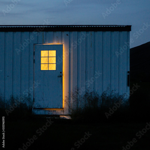 Mysterious creepy ajar door at night, with yellow light through window Canvas Print