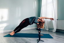 Young Woman In Sportswear Doing Yoga And Blogging With A Mobile Phone And A Gimbal