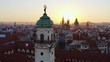 Aerial footage old town district in Prague at sunrise. Cityscape from high, drone flying forward above red tiled roof of buildings between ancient towers with decorated spires in sunny morning