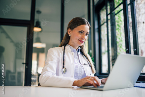 Positive doctor working on laptop in medical office, portrait.