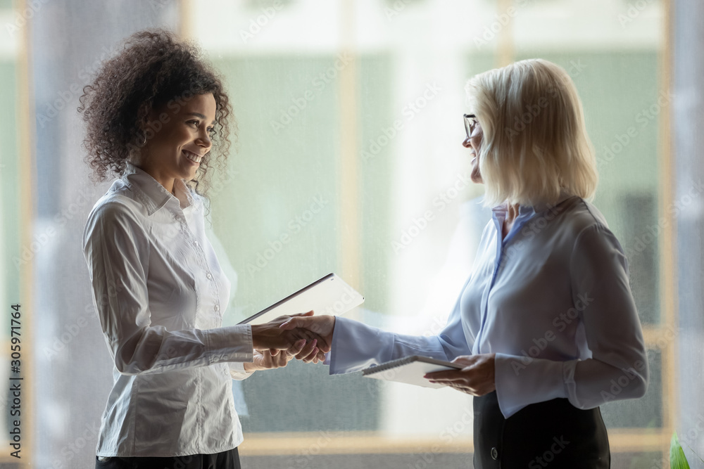 Fototapeta Smiling diverse businesswomen shake hands greeting in office