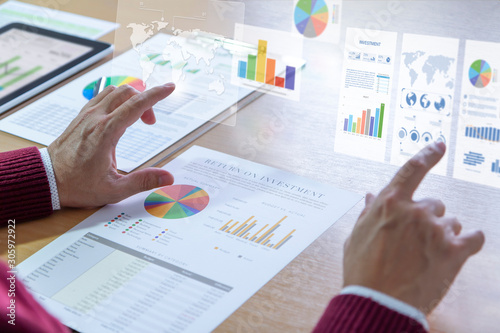 Photo Businessman interacts with augmented reality graphics while deeply reviewing a financial report for a return on investment or investment risk analysis