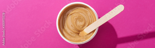 Fototapeta top view of depilation wax in cup with stick on pink background, panoramic shot obraz na płótnie